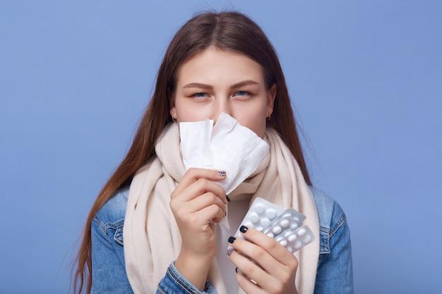 Porträt der jungen frau, die erkältung fängt und pillen in den händen hält