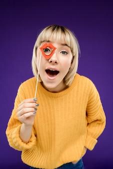 Porträt der jungen frau, die falsche lippen über lila wand trägt