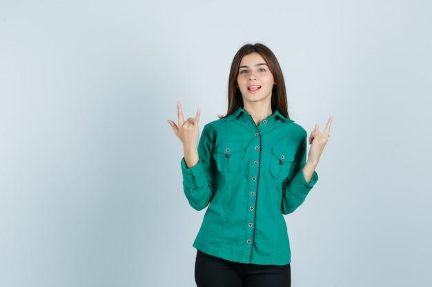 Porträt der jungen frau, die felsengeste zeigt, zunge in grünem hemd herausstreckt und glückliche vorderansicht schaut
