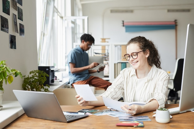 Porträt der jungen frau, die fotografien überprüft, während sie an der bearbeitung und veröffentlichung im modernen büro arbeitet, kopiert raum