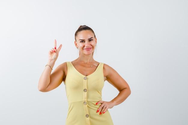 Porträt der jungen frau, die friedensgeste im gelben kleid zeigt und fröhliche vorderansicht schaut
