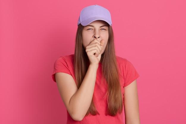 Porträt der jungen frau, die gähnt. müde weibliche aufstellung lokalisiert über rosa wand