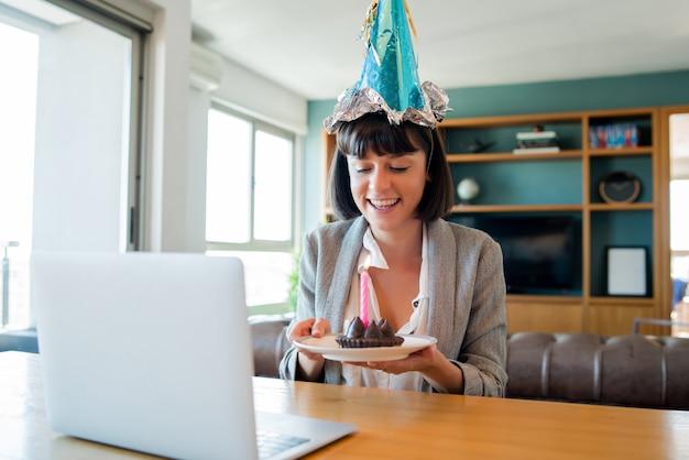 Porträt der jungen frau, die geburtstag auf einem videoanruf mit laptop und kuchen von zu hause feiert. neues normales lifestyle-konzept.