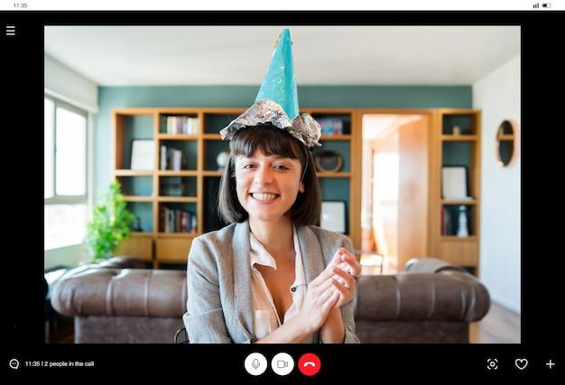 Porträt der jungen frau, die geburtstag auf einem videoanruf von zu hause feiert. frau, die geburtstag online in der quarantänezeit feiert. neues normales lifestyle-konzept.