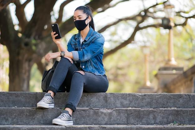 Porträt der jungen frau, die gesichtsmaske trägt und ihr handy benutzt, während auf treppen draußen sitzt