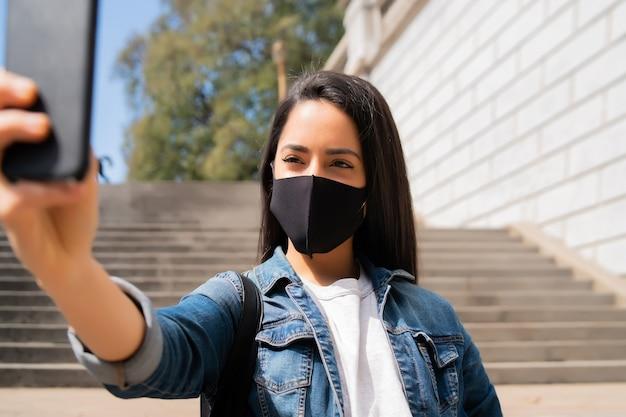 Porträt der jungen frau, die gesichtsmaske trägt und selfies mit ihrem mophilen telefon nimmt, während sie draußen steht