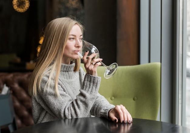 Porträt der jungen frau, die glas wein genießt