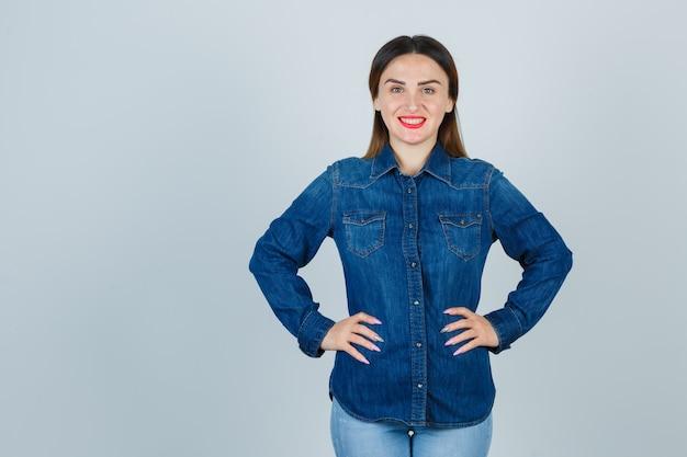 Porträt der jungen frau, die hände auf hüfte im jeanshemd und in den jeans hält und herrliche vorderansicht schaut