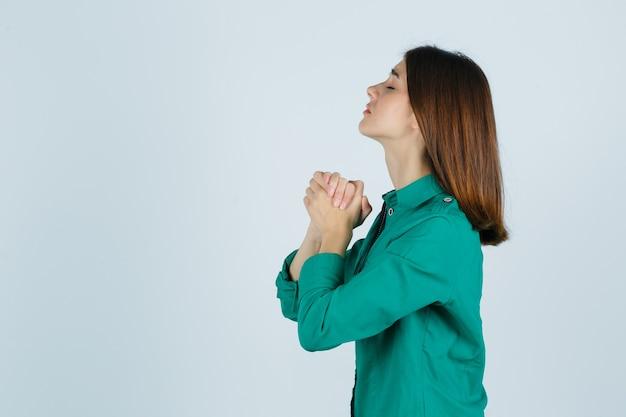 Porträt der jungen frau, die hände in der gebetsgeste im grünen hemd fasst und hoffnungsvoll schaut