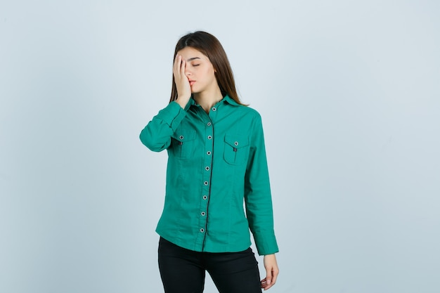 Porträt der jungen frau, die hand auf gesicht im grünen hemd, in der hose und in der müden vorderansicht hält