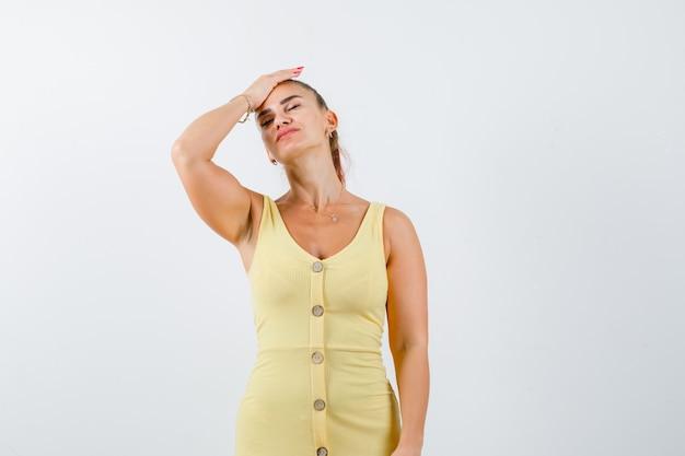 Porträt der jungen frau, die hand auf kopf im gelben kleid hält und vergessliche vorderansicht schaut