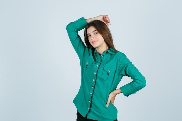 Porträt der jungen frau, die hand auf kopf im grünen hemd hält und fröhliche vorderansicht schaut