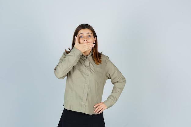 Porträt der jungen frau, die hand auf mund in hemd, rock hält und schockiert schaut