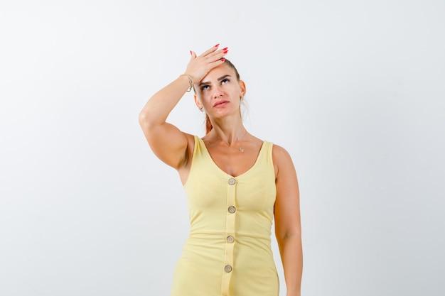 Porträt der jungen frau, die hand auf stirn hält, im gelben kleid nach oben schauend