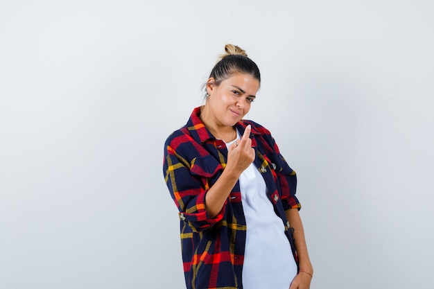 Porträt der jungen frau, die hierher kommt, geste mit der hand, seitlich im karierten hemd stehend und attraktiv aussehend.