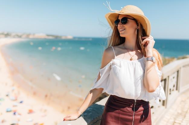 Porträt der jungen frau, die hut und runde sonnenbrille trägt, windiges wetter schöner sommertag auf ozean