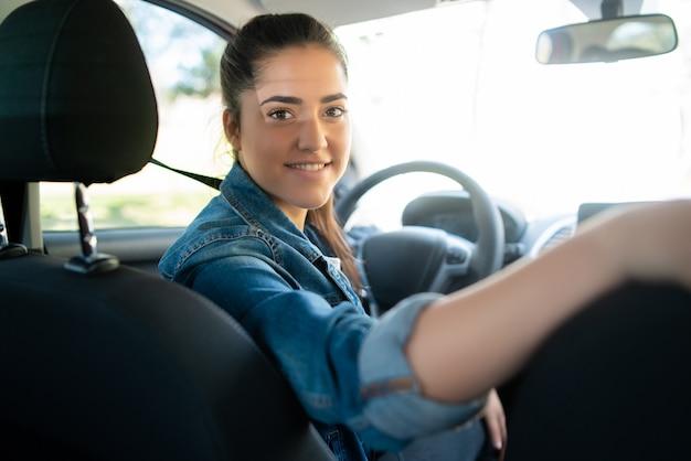 Porträt der jungen frau, die ihr auto fährt und rücksitz betrachtet