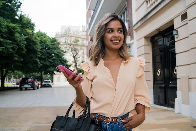 Porträt der jungen frau, die ihr handy benutzt, während sie draußen auf der straße geht
