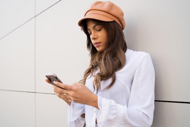 Porträt der jungen frau, die ihr handy benutzt, während sie draußen auf der straße steht. stadt- und kommunikationskonzept.