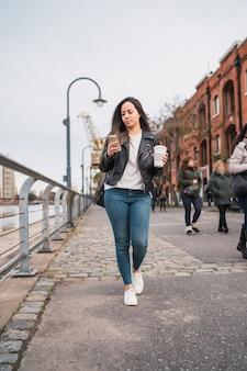 Porträt der jungen frau, die ihr handy benutzt, während sie mit tasse kaffee geht. stadt- und kommunikationskonzept.