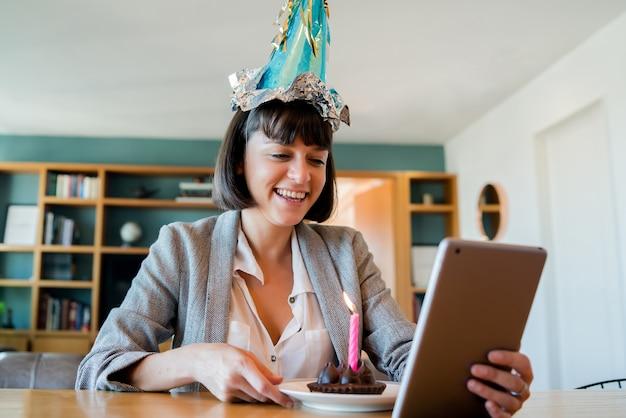 Porträt der jungen frau, die ihren geburtstag auf einem videoanruf mit digitalem tablett und einem kuchen zu hause feiert
