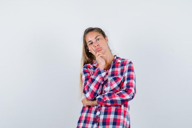 Porträt der jungen frau, die in der denkenden haltung im freizeithemd steht und vernünftige vorderansicht schaut