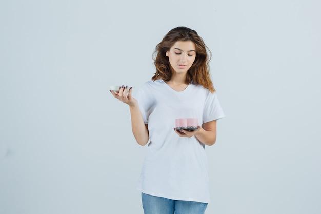 Porträt der jungen frau, die in geschenkbox in weißem t-shirt, jeans schaut und erstaunte vorderansicht schaut