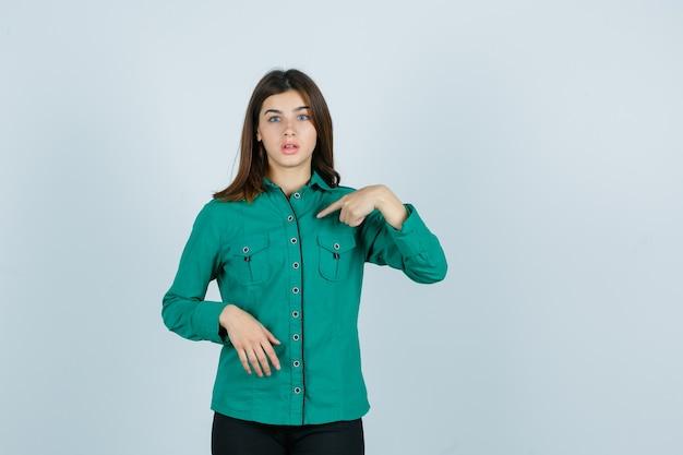 Porträt der jungen frau, die in grünem hemd auf sich zeigt und verwirrte vorderansicht schaut