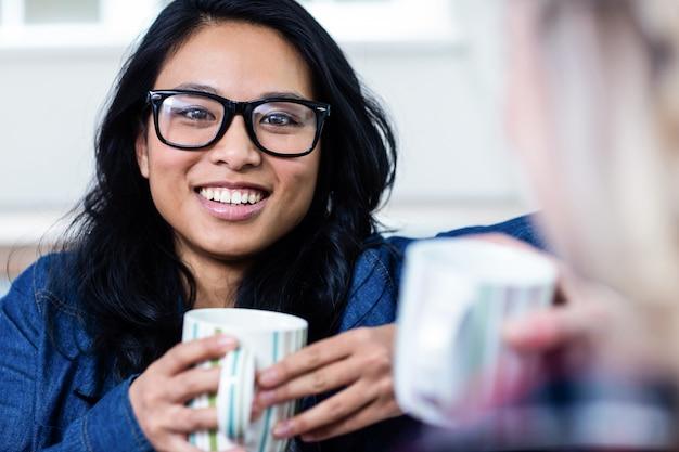 Porträt der jungen frau, die kaffee mit freund trinkt