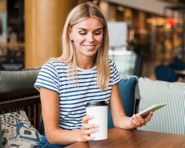 Porträt der jungen frau, die kaffeetasse genießt