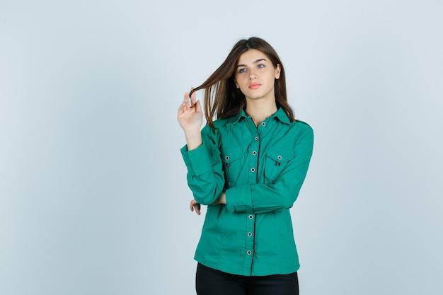 Porträt der jungen frau, die kastanienbraunes haar um ihre finger im grünen hemd wirbelt und nachdenkliche vorderansicht schaut