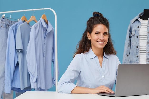 Porträt der jungen frau, die lächelt, während sie am tisch sitzt und am laptop im bekleidungsgeschäft arbeitet