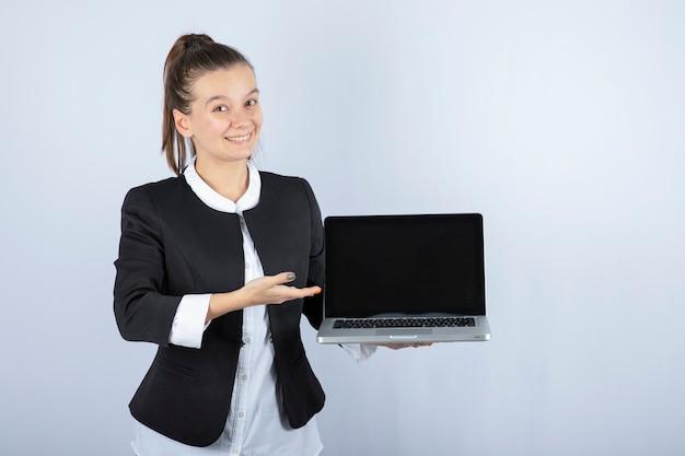 Porträt der jungen frau, die laptop über weißer wand hält.