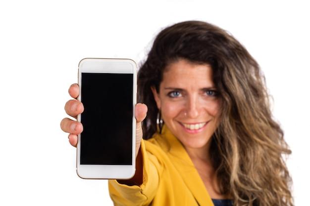 Porträt der jungen frau, die leeren smartphonebildschirm zeigt und die kamera über weißem hintergrund betrachtet.