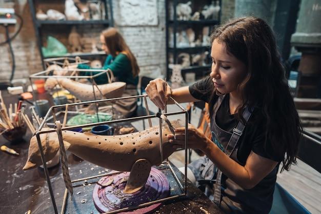 Porträt der jungen frau, die lieblingsjob in der werkstatt genießt. potter arbeitet sorgfältig am tonwal