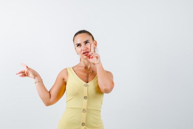 Porträt der jungen frau, die links zeigt, finger auf wange im gelben kleid hält und nachdenkliche vorderansicht schaut