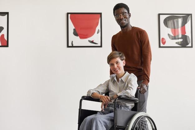 Porträt der jungen frau, die maske trägt und beim besuch des museums für moderne kunst mit afroamerikanischem mann hilft,