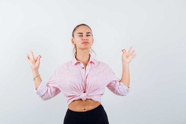Porträt der jungen frau, die meditationsgeste im freizeithemd zeigt und friedliche vorderansicht schaut