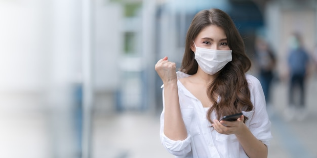 Porträt der jungen frau, die medizinische gesichtsmaskenschutz mit einem telefon trägt, geht in eine stadt