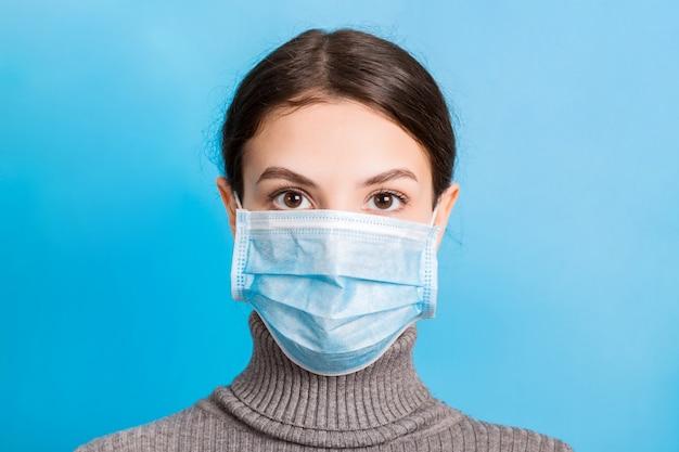 Porträt der jungen frau, die medizinische maske bei blau trägt. schützen sie ihre gesundheit. coronavirus-konzept