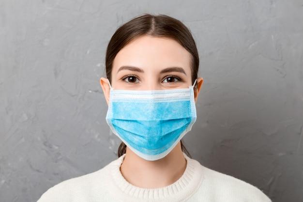 Porträt der jungen frau, die medizinische maske trägt