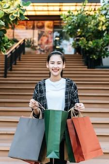 Porträt der jungen frau, die mehrere einkaufstüten aus papier trägt