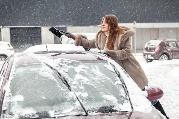 Porträt der jungen frau, die mit bürste schnee vom autodach säubert