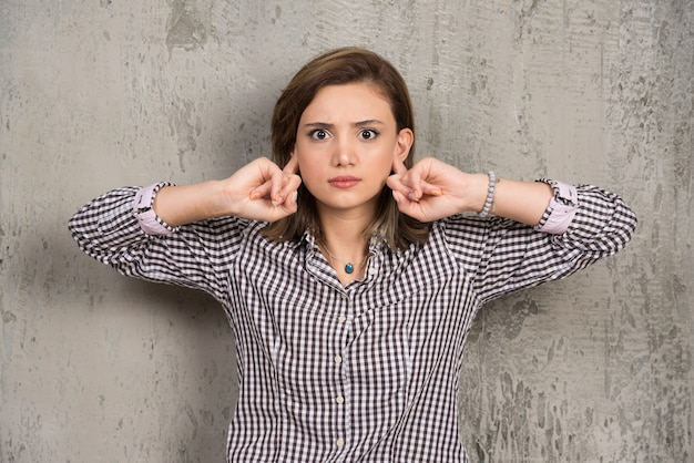 Porträt der jungen frau, die mit den händen ihre ohren bedeckt