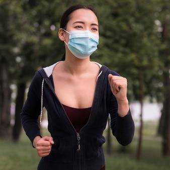 Porträt der jungen frau, die mit der chirurgischen maske läuft
