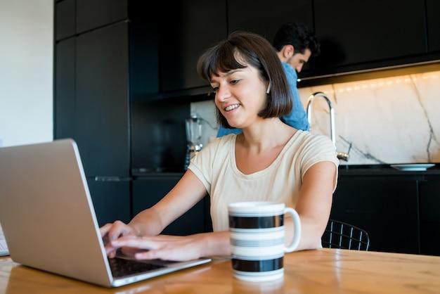 Porträt der jungen frau, die mit einem laptop von zu hause aus arbeitet, während mann küche reinigt