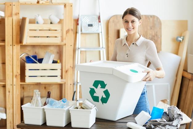 Porträt der jungen frau, die mit großem plastikbehälter für müll steht und im lager lächelt