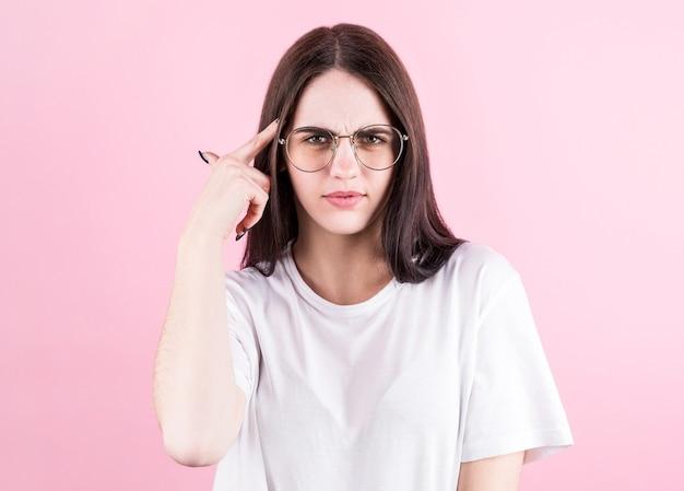 Porträt der jungen frau, die mit ihrem finger zu ihrem kopf lokalisiert über rosa hintergrund denkt