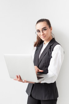 Porträt der jungen frau, die mit laptop aufwirft