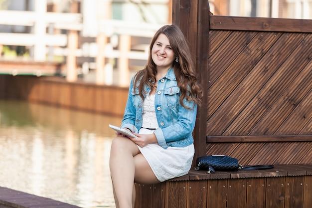 Porträt der jungen frau, die mit tablette auf bank gegen fluss sitzt